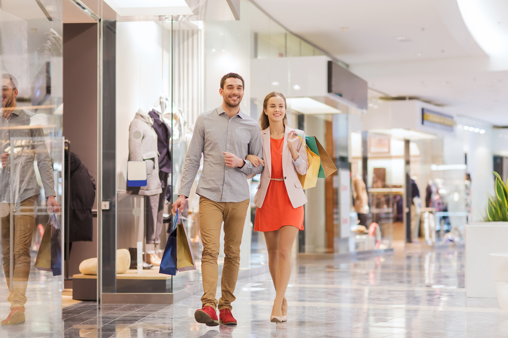 young couple with shopping bags walking
